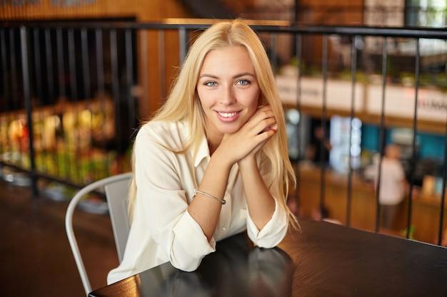Kryty portret pięknej młodej blondynki długowłosej kobiety pozującej nad wnętrzem kawiarni, patrząc z czarującym uśmiechem i opierając głowę na skrzyżowanych ramionach