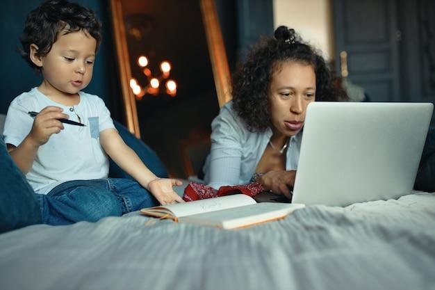 Kryty portret pięknej młodej samicy pracującej zdalnie z domu, leżąc na łóżku z laptopem, podczas gdy jej śliczny synek trzyma ołówek