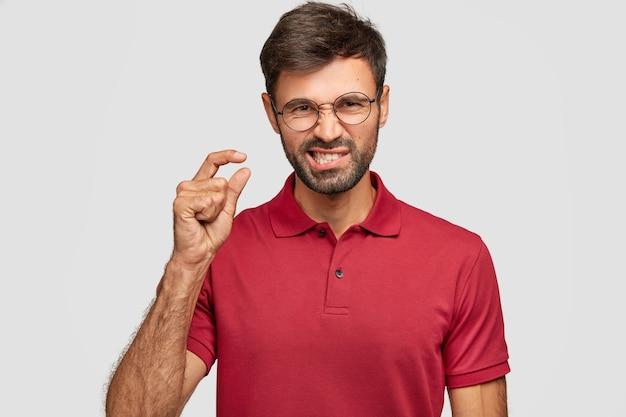 Kryty portret przystojnego niezadowolonego, nieogolonego młodego mężczyzny marszczy brwi z niezadowoleniem, gestykuluje ręką, pokazuje coś bardzo małego, ubranego w czerwoną koszulkę, odizolowanego na białej ścianie