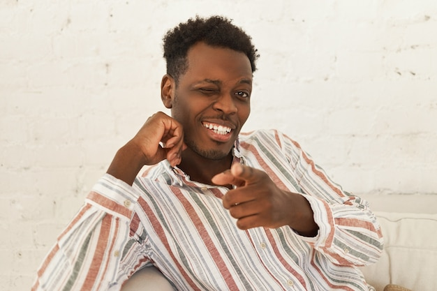 Kryty portret przystojny wesoły pozytywny młody ciemnoskóry mężczyzna w stylowej koszuli siedzi na kanapie i mrugając