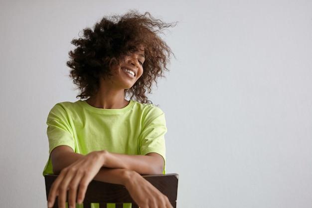 Kryty portret szczęśliwej młodej kręconej kobiety o ciemnej skórze pozuje na krześle, macha głową i uśmiecha się radośnie, trzymając ręce skrzyżowane