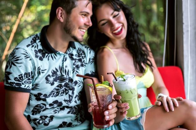 Kryty portret szczęśliwej stylowej pary cieszącej się romantyczną randką, pijącej smaczne słodkie napoje alkoholowe, eleganckie ubrania, elegancka restauracja.