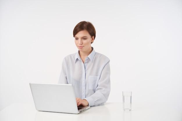 Kryty portret uroczej młodej krótkowłosej brunetki z przypadkową fryzurą, trzymając rękę na klawiaturze i wpisując tekst na laptopie, na białym tle