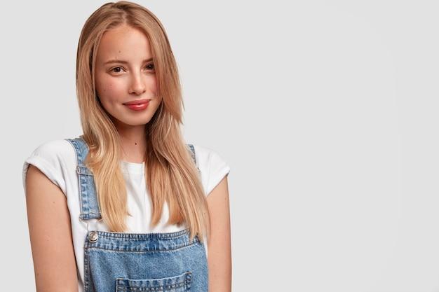 Kryty strzał atrakcyjnej młodej kobiety z jasnymi prostymi włosami, odpoczywa po spacerze na świeżym powietrzu, nosi modny dżinsowy kombinezon, stoi na białej ścianie z copyspace