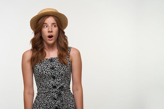 Kryty strzał atrakcyjnej zdumionej młodej kobiety z lśniącymi falującymi włosami, pozująca na białym tle w letniej sukience i kapeluszu, patrząca na bok z przytłoczoną twarzą i szeroko otwartymi ustami