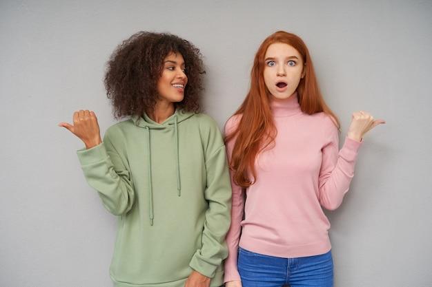Kryty strzał atrakcyjnych młodych kobiet ściskających ręce i wskazujących w różnych kierunkach, pokazujących różne emocje, stojąc na szarej ścianie