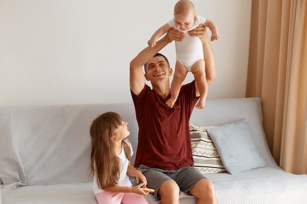Kryty strzał brunetka młody dorosły mężczyzna rasy kaukaskiej ubrany w stylu casual bordową koszulkę pozuje w salonie w domu, siedząc na kanapie z dwójką dzieci, rzucając się niemowlę dziecko.