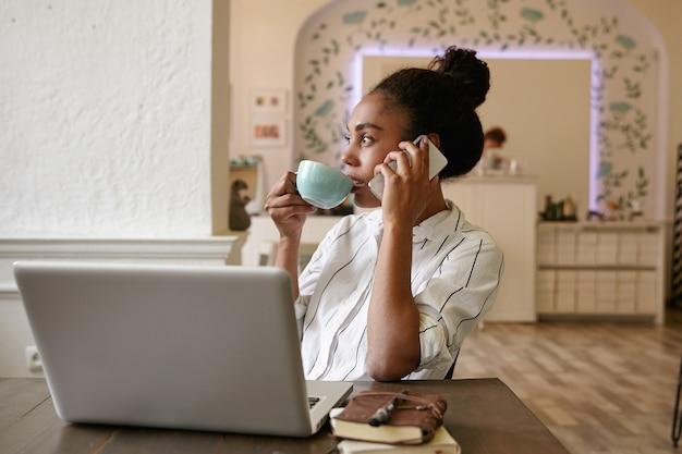 Kryty strzał całkiem młoda kobieta o ciemnej skórze, pracująca poza biurem z nowoczesnym laptopem, pije kawę i patrząc na bok w zamyśleniu
