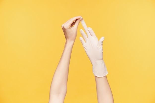 Kryty strzał dłoni młodej kobiety o jasnej karnacji, ciągnąc białą rękawiczkę z drugiej strony środkowym palcem, odizolowane na pomarańczowym tle. koncepcja ludzkich rąk