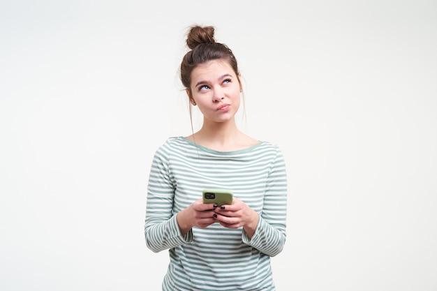 Kryty strzał młoda zamyślona śliczna brunetka kobieta trzymając smartfon w uniesionych rękach, patrząc w górę w zamyśleniu, na białym tle nad białą ścianą