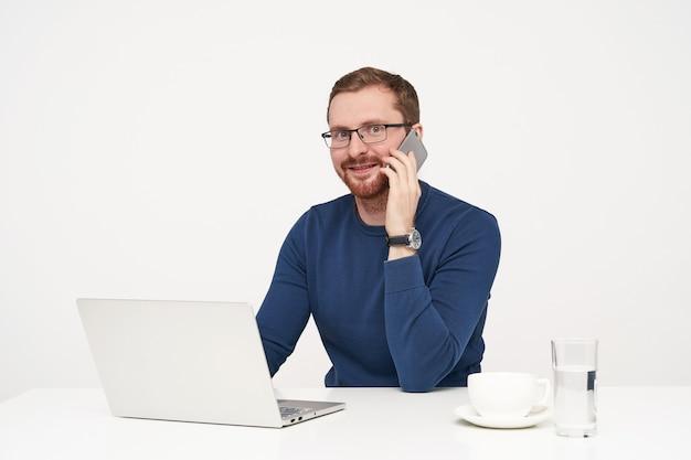 Kryty strzał młodego brodatego mężczyzny w okularach, trzymając telefon komórkowy w uniesionej ręce, mając przyjemną rozmowę i zaskoczony patrząc na kamery, odizolowane na białym tle