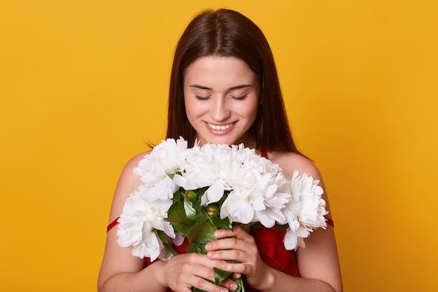 Kryty strzał młodej kobiety słodkie, pachnące białe kwiaty, patrząc w dół na jej bukiet, trzymając w rękach delikatne piwonie