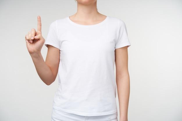 Kryty strzał młodej kobiety, trzymając podniesiony palec wskazujący, pokazując literę d na języku migowym, stojąc na białym tle w codziennym noszeniu