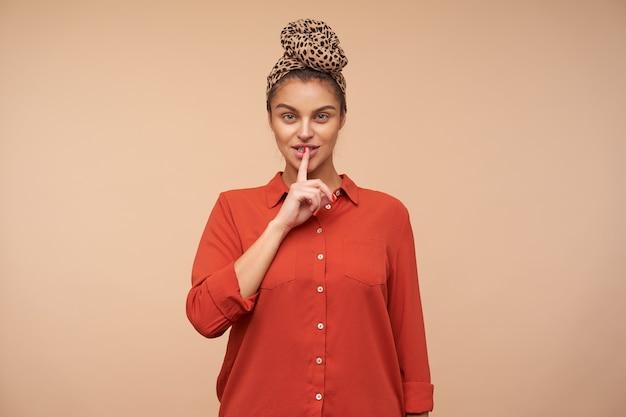 Kryty strzał młodej ładnej brunetki kobiety podnoszącej rękę w geście wyciszenia, proszącej o zachowanie ciszy, odizolowanej na beżowej ścianie w opasce i czerwonej koszuli