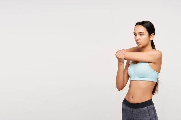 Kryty strzał młodej szczupłej brązowowłosej kobiety ubranej w miętowy top i szare legginsy, rozciągającej ręce przed treningiem, stojąc na białej ścianie