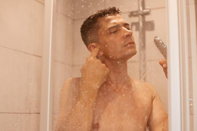 Kryty strzał młody dorosły atrakcyjny ciemnowłosy mężczyzna, czyszczenie ucha podczas brania prysznica i stojąc pod gorącą wodą w kafelkowej kabinie prysznicowej, procedury higieny.