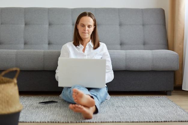 Kryty strzał młodych dorosłych freelancerów pracujących online, siedzących na podłodze w pobliżu szarej sofy, patrzących na wyświetlacz komputera pc, kobiety ubranej w białą koszulę i dżinsy.