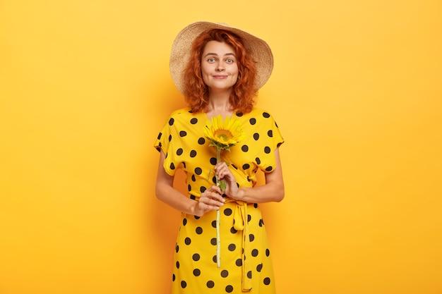 Kryty strzał piękna uśmiechnięta rudowłosa kobieta posiada słonecznik