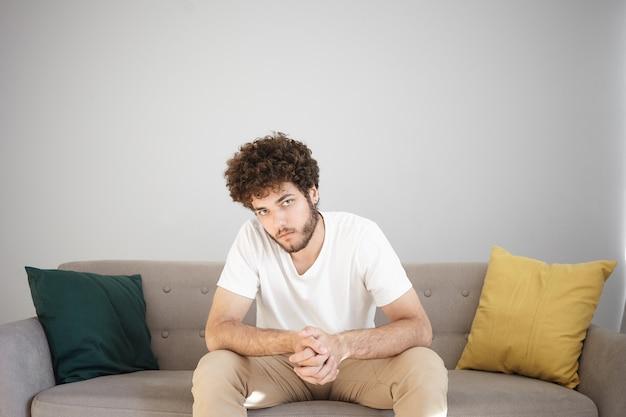 Kryty strzał poważnego przystojnego młodego, nieogolonego modelu męskiego w białej koszulce i beżowych dżinsach pozuje w nowoczesnym przytulnym salonie przy białej ścianie, siedzi na kanapie, ściskając ręce i