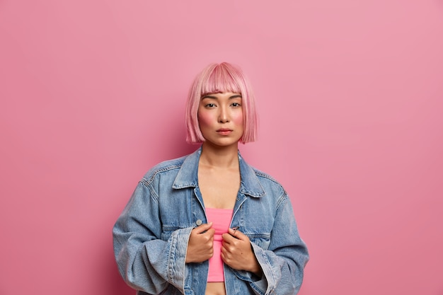 Kryty strzał poważnej różowowłosej modelki ubranej w górną i obszerną dżinsową kurtkę, wygląda bezpośrednio, nosi minimalny makijaż,