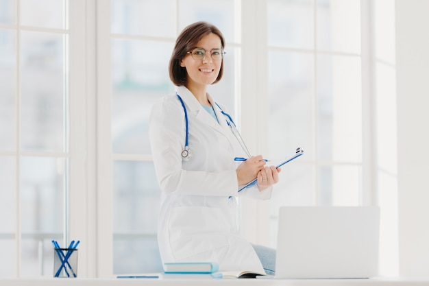 Kryty strzał profesjonalnej kobiety lekarz dostarcza pomoc medyczną, pozy na pulpicie z laptopem