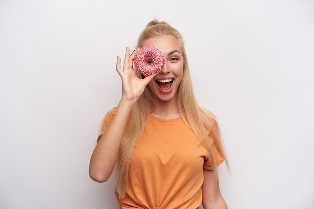 Kryty strzał radosnej atrakcyjnej młodej blondynki z przypadkową fryzurą, śmiejąc się z pączkiem w uniesionej ręce, patrząc wesoło na kamerę, odizolowane na białym tle
