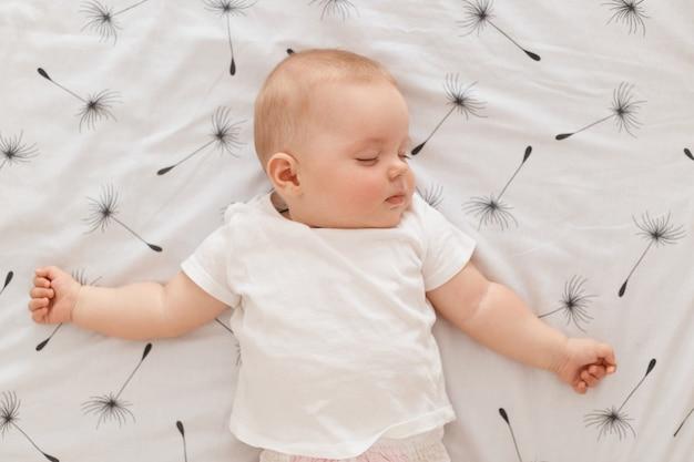 Kryty strzał ślicznego uroczego uroczego dziecka śpiącego na łóżku, noszącego białą koszulkę, trzymającego zamknięte oczy, malucha śpiącego po południu, szczęśliwego beztroskiego dzieciństwa.