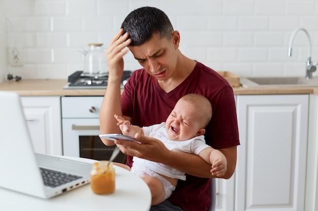 Kryty strzał smutnego ojca noszącego bordową casualową koszulkę siedzącego z chłopcem lub dziewczynką w kuchni, trzymającego inteligentny telefon, wybierającego numer żony, nie może uspokoić córki lub syna.