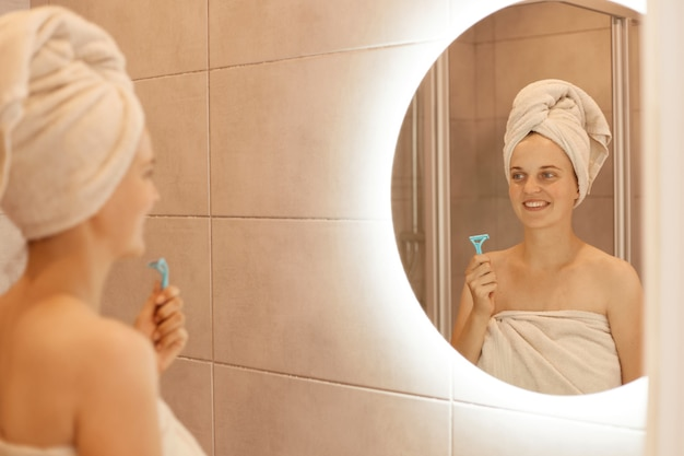 Kryty strzał szczęśliwa młoda dorosła kobieta trzyma brzytwę do golenia pod pachami w ręku, pozowanie w łazience przed depilacją, patrząc na odbicie lustrzane, procedury higieniczne.
