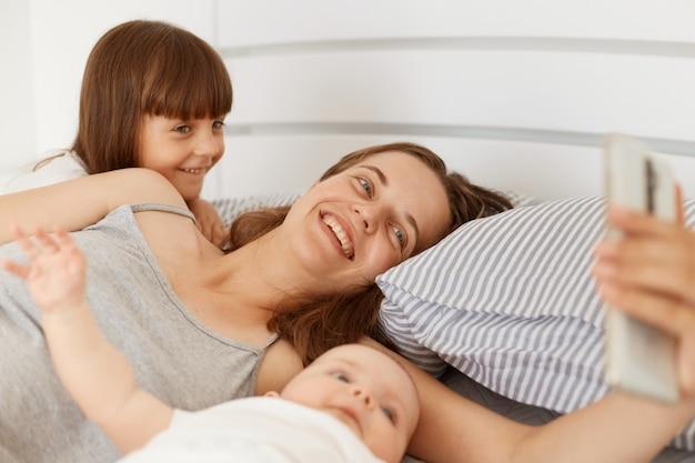 Kryty strzał szczęśliwa uśmiechnięta kobieta ubrana w szarą koszulkę bez rękawów, leżącą w łóżku z dziećmi i trzymającą smartfon w rękach, po rozmowie wideo z mężem.