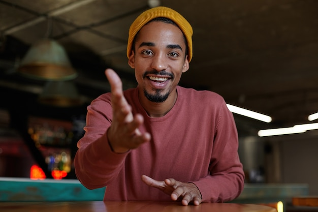 Kryty strzał szczęśliwego młodego, brodatego ciemnoskórego mężczyzny siedzącego nad wnętrzem kawiarni w swobodnym ubraniu i patrzącego radośnie z szerokim radosnym uśmiechem, pokazując przed sobą z uniesioną dłonią
