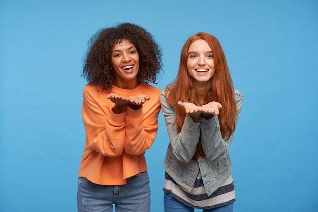Kryty strzał szczęśliwych młodych atrakcyjnych kobiet, patrząc pozytywnie z szerokim przyjemnym uśmiechem i trzymając ręce podniesione, odizolowane na niebieskiej ścianie