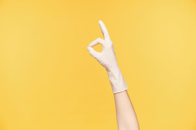 Kryty strzał uniesionej kobiecej dłoni w gumowej białej rękawiczce tworzącej z dobrze wykonanym gestem palców, kończącej wiosenne porządki i zadowolonej, pozując na pomarańczowym tle
