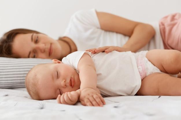 Kryty strzał uśmiechniętej kobiety leżącej ze śpiącą córką, odpoczywającą razem z jej uroczym dzieckiem, kobieta ubrana w białą koszulkę dorywczo patrzącą na niemowlę dziewczynę z pozytywnymi emocjami.