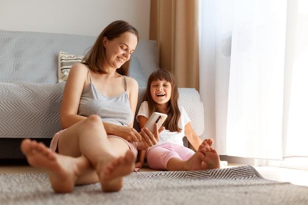 Kryty strzał uśmiechniętej optymistycznej kobiety siedzącej na podłodze w pobliżu sofy i okna z jej uroczą córką i trzymającą telefon w rękach, rodzina śmiejąc się szczęśliwie.