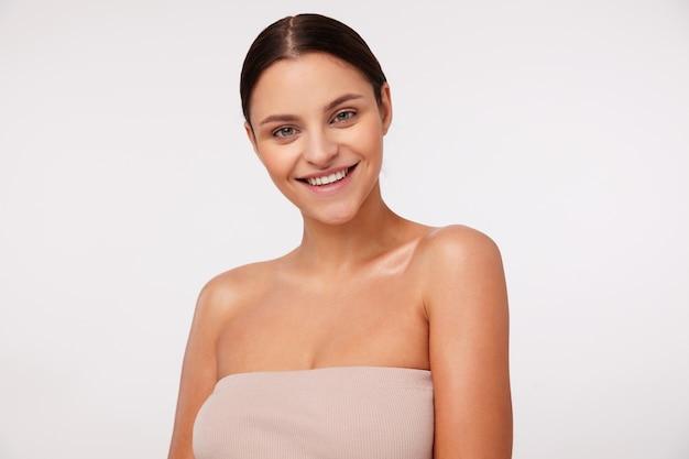 Kryty strzał wesoła młoda ładna brunetka kobieta z naturalnym makijażem, patrząc z czarującym uśmiechem stojąc, będąc w dobrym nastroju