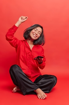 Kryty strzał wesołej miłośniczki muzyki słucha ulubionej piosenki w bezprzewodowych słuchawkach, siedzi ze skrzyżowanymi nogami, cieszy się miłym relaksującym dniem, tańczy do rytmu, korzysta z aplikacji muzycznej do medytacji online