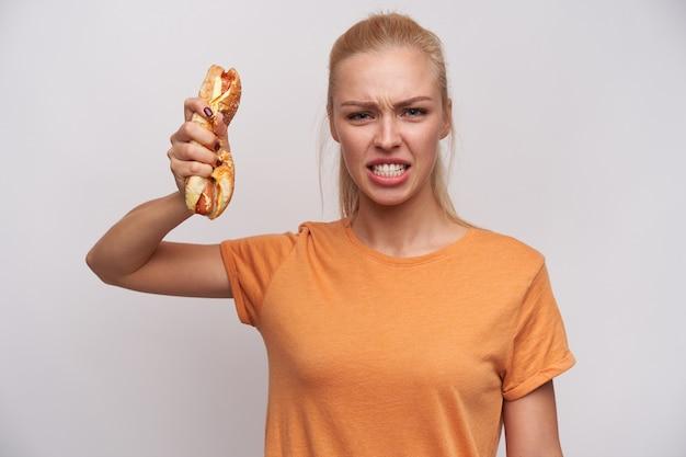 Kryty strzał wściekłej młodej ładnej blondynki kobiety ubranej w zwykłe ubrania, patrząc gwałtownie w kamerę i zgniatającego hot doga w uniesionej dłoni, stojąc na białym tle