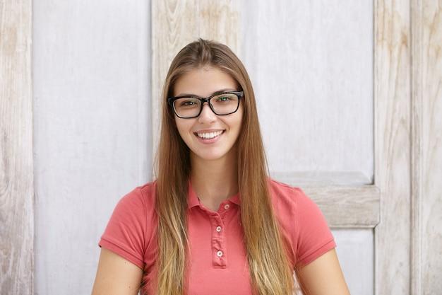Kryty strzał z piękną młodą kobietą rasy kaukaskiej na sobie koszulkę polo i prostokątne okulary uśmiechając się radośnie podczas pozowanie na białym tle