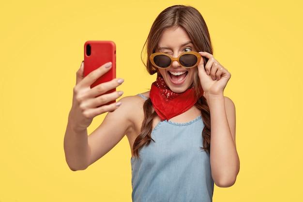 Kryty strzał zadowolonej młodej brunetki w okularach przeciwsłonecznych, pozowanie na żółtej ścianie