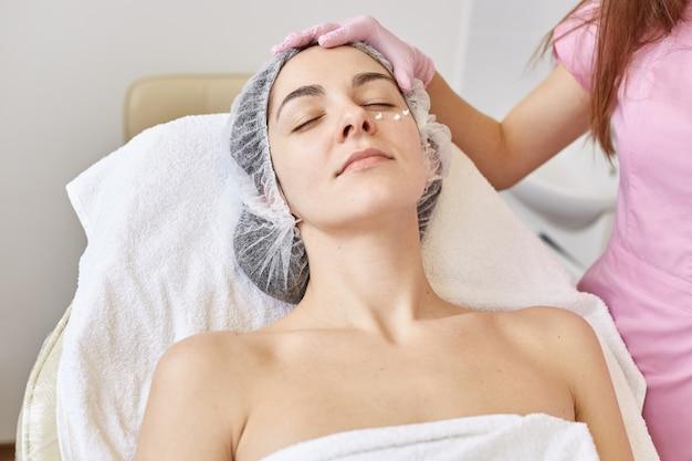 Kryty strzał zadowolonej zrelaksowanej kobiety zamykającej oczy, leżącej na trenerze, korzystającej z usług kosmetycznych, odżywczej krem pod oczy, spędzającej czas w salonie spa.