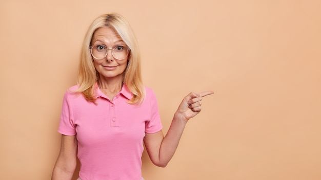 Kryty strzał zaskoczony blond europejką wskazuje na puste miejsce przedstawia specjalną ofertę nosi przezroczyste okulary i różową koszulkę na białym tle nad beżową ścianą