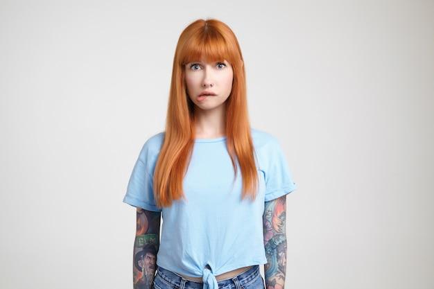 Kryty strzał zdezorientowanej młodej, długowłosej rudowłosej pani z tatuażami gryzącymi usta, patrząc z niepokojem w kamerę, pozuje na białym tle