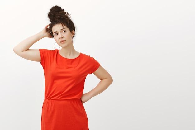 Kryty strzał zdezorientowanej pytającej ładnej kobiety z kręconymi włosami w modnej czerwonej sukience