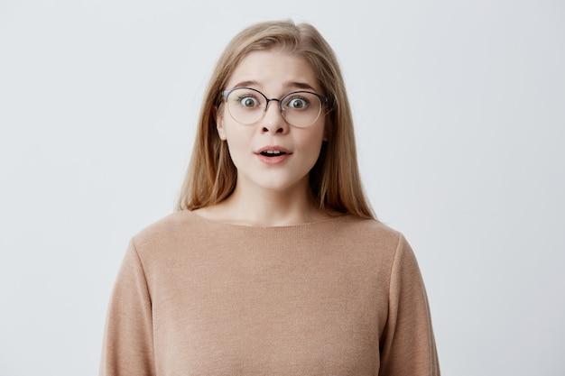 Kryty strzał zszokowanej blondynki w swetrze i okularach wygląda z szerokimi oczami, przerażony faktem, że jej przyjaciółka jest w szpitalu, zastanawia się, jak to się stało. szokujące wiadomości
