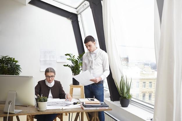 Kryty ujęcie atrakcyjnej, doświadczonej, dojrzałej kobiety architekt siedzącej przy biurku i sprawdzającej rysunki techniczne jej ambitnego, wykwalifikowanego młodego kolegi. ludzie, praca, zawód i współpraca