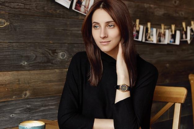 Kryty ujęcie atrakcyjnej, zamyślonej młodej europejskiej kobiety korzystającej z wolnego czasu samotnie, pijąc herbatę lub kawę, mając zamyślony i marzycielski wygląd, siedząc przy stoliku kawiarnianym z kubkiem. ludzie i styl życia