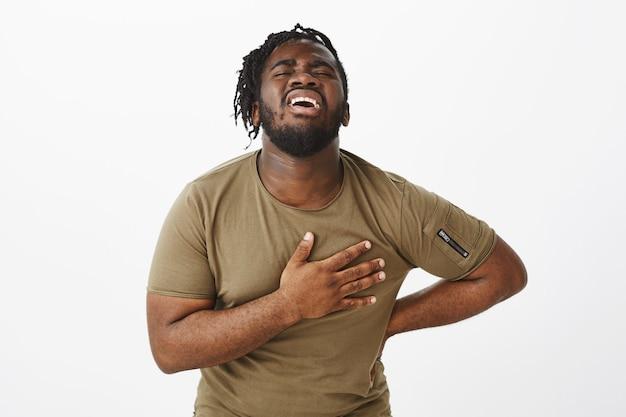 Kryty ujęcie cierpiącego faceta w brązowej koszulce, pozującego przy białej ścianie