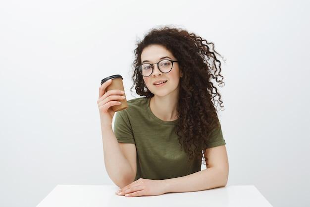 Kryty ujęcie dobrze wyglądającej, zabieganej kobiety z kręconymi włosami w okularach, siedzącej przy stole i pijącej kawę, czekającej na klienta w lokalnej kawiarni