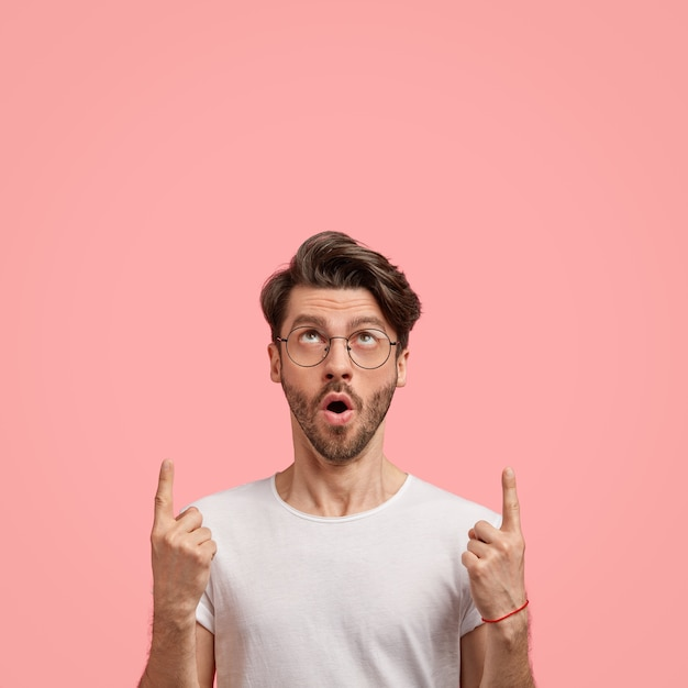 Kryty ujęcie emocjonalnego, nieogolonego mężczyzny z modną fryzurą, ciemne włosie, otwiera usta ze zdumienia, wskazuje dwoma palcami wskazującymi, pokazuje wolne miejsce na treści promocyjne, ubrany swobodnie
